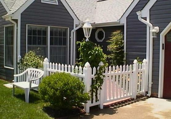 White vinyl fencing in front of a blue house in Largo, FL